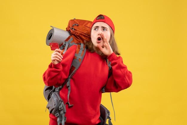 Vue de face jolie randonneuse avec sac à dos tenant une carte de crédit appelant quelqu'un