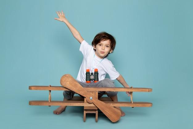 Vue de face jouant garçon en t-shirt blanc sur bleu