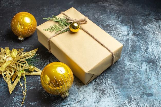 Vue de face des jouets d'arbre de noël avec un cadeau sur une photo de couleur clair-foncé noël nouvel an