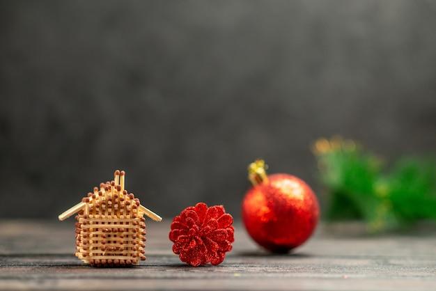 Vue de face des jouets d'arbre de noël correspondent à la maison sur un espace libre sombre