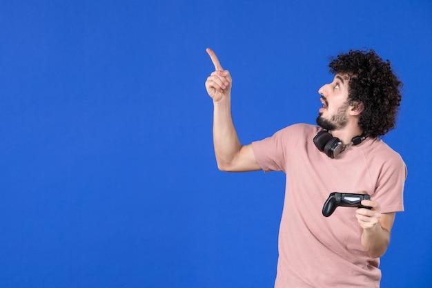 Vue de face joueur masculin avec manette de jeu sur fond bleu jeune joueur de football virtuel jeunesse de l'adolescence gagnant la joie des adultes