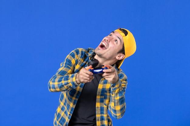 Vue de face d'un joueur masculin avec une manette de jeu jouant à un jeu vidéo sur un mur bleu