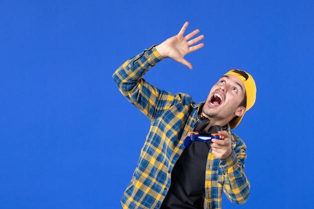 Vue de face d'un joueur masculin avec une manette de jeu jouant à un jeu vidéo et regardant au-dessus sur un mur bleu