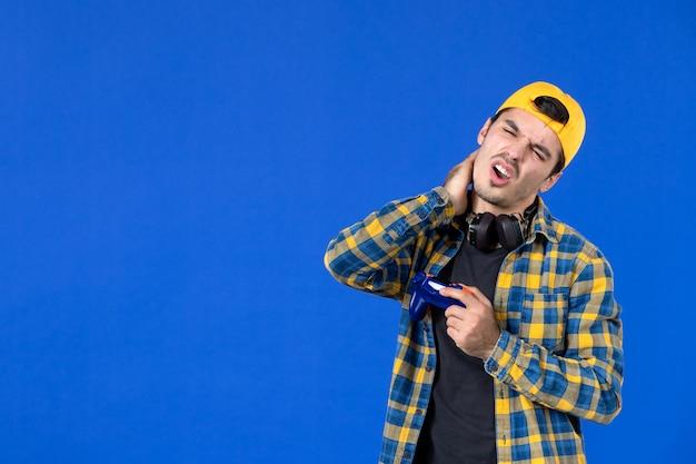 Vue de face d'un joueur masculin avec une manette de jeu orange jouant à un jeu vidéo sur un mur bleu