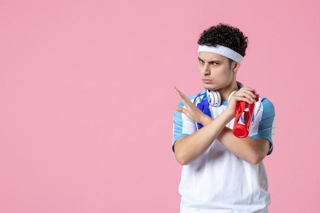 Vue de face joueur masculin en vêtements de sport avec une bouteille d'eau