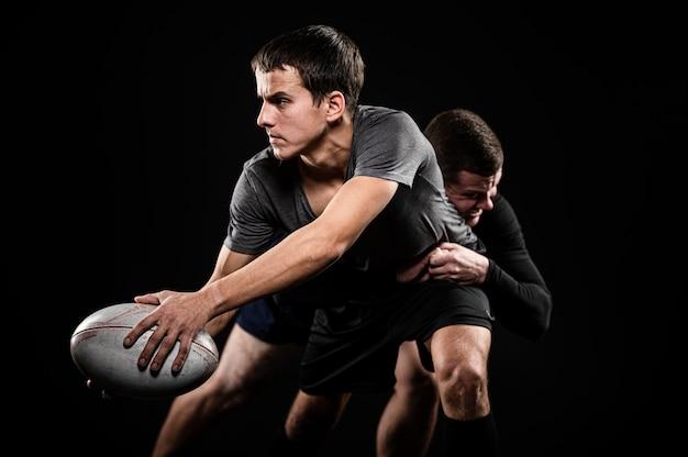 Vue de face des joueurs de rugby masculins avec ballon
