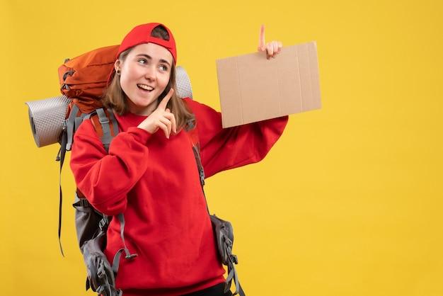 Vue de face joyeuse auto-stoppeuse tenant un carton vierge