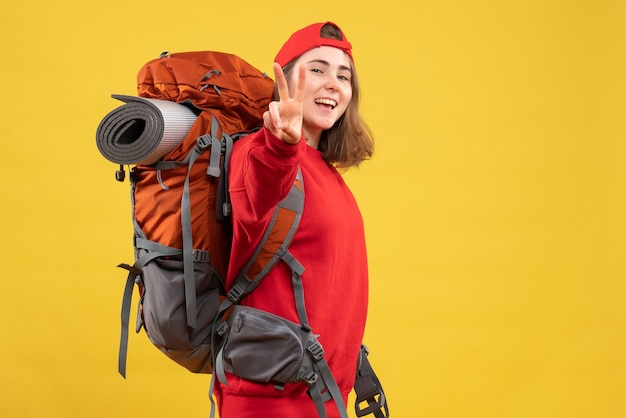 Vue de face joyeuse voyageuse avec sac à dos gesticulant signe de la victoire