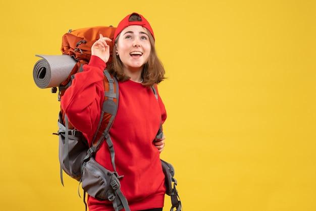 Vue de face joyeuse voyageuse avec sac à dos en levant