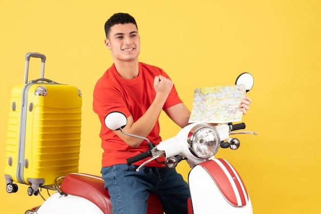Vue de face joyeux bel homme sur la carte de tenue de cyclomoteur