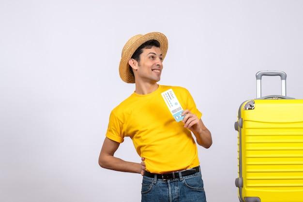 Vue de face joyeux jeune touriste debout près de valise jaune tenant un billet de voyage
