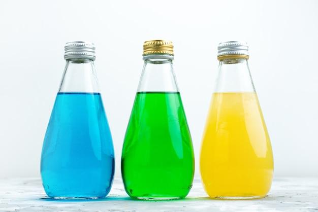 Une vue de face jus colorés à l'intérieur de bouteilles en verre sur blanc, couleur de jus de boisson