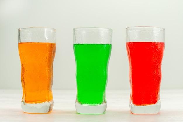 Vue de face jus colorés à l'intérieur de longs verres sur une surface blanche