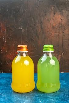 Vue de face des jus de fruits rafraîchissants à l'intérieur des bouteilles de conserve sur de la limonade de boisson de jus de fruits de couleur foncée