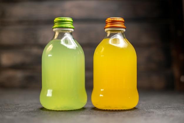 Vue de face jus orange et jaune en bouteille