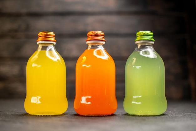 Vue de face jus orange et vert jaune en bouteilles