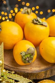 Vue de face des kakis frais autour des jouets de noël sur fond sombre jus de fruits frais exotiques tropicaux