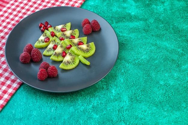 Vue de face de kiwis frais tranchés avec des framboises à l'intérieur de la plaque sur une surface verte photo jus exotique fruits tropicaux couleur berry