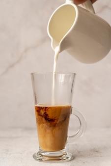 Vue de face lait versé dans le café glacé