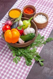 Vue de face légumes frais avec assaisonnements sur fond sombre salade mûre nourriture santé déjeuner