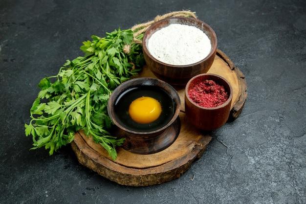 Vue de face des légumes frais avec de la farine et des œufs sur l'espace gris