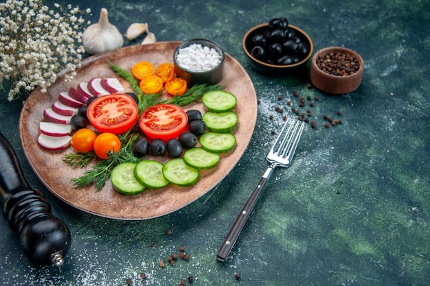 Vue de face de légumes frais hachés olives sel dans une assiette brune et fleur d'ail marteau de cuisine sur fond de couleurs mélangées noir vert