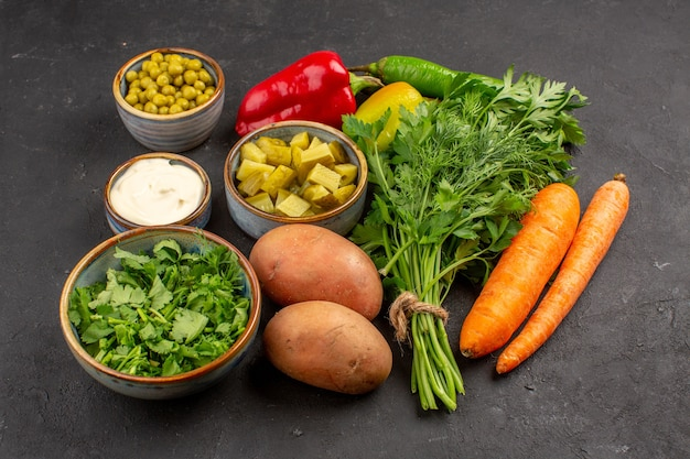 Vue de face de légumes frais avec des verts sur une surface sombre