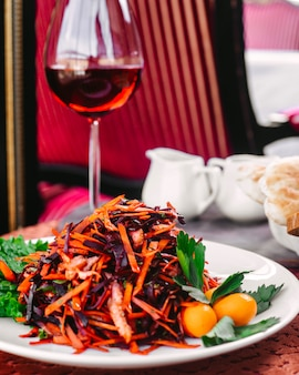 Une vue de face des légumes frits avec salade verte à l'intérieur de la plaque blanche sur la table