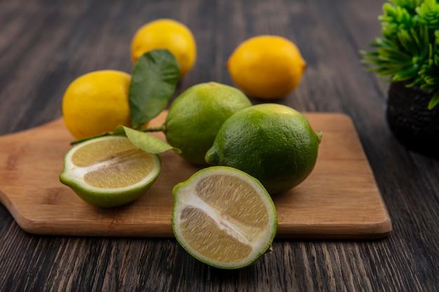 Vue de face limes coupées en deux sur une planche à découper avec des citrons sur un fond en bois