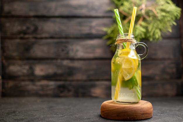 Vue de face limonade aromatisée par des pipettes jaunes et vertes à la menthe sur des plantes en pot de planche de bois à la surface