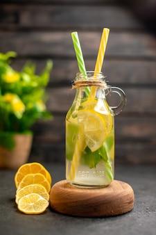 Vue de face limonade sur planche de service en bois tranches de citron plante en pot sur surface brune