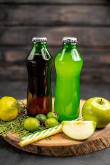 Vue de face limonade verte noire dans des bouteilles pipettes feijoas pomme citron sur planche de bois