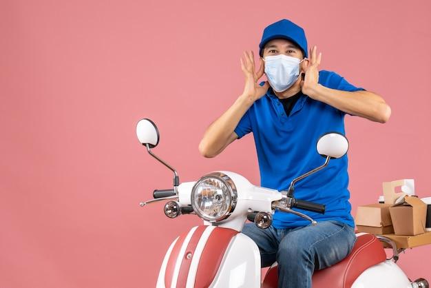 Vue de face d'un livreur choqué en masque médical portant un chapeau assis sur un scooter sur fond de pêche pastel