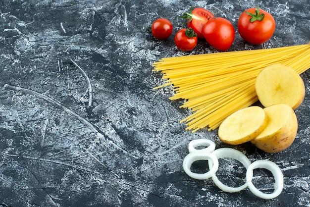 Vue de face de longues pâtes crues aux tomates rouges sur fond gris couleur de cuisson salade cuisine cuisine végétale nourriture