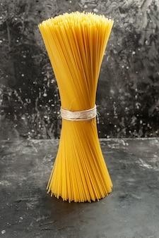 Vue de face de longues pâtes italiennes crues sur le repas photo de cuisine de pâte de couleur alimentaire gris clair