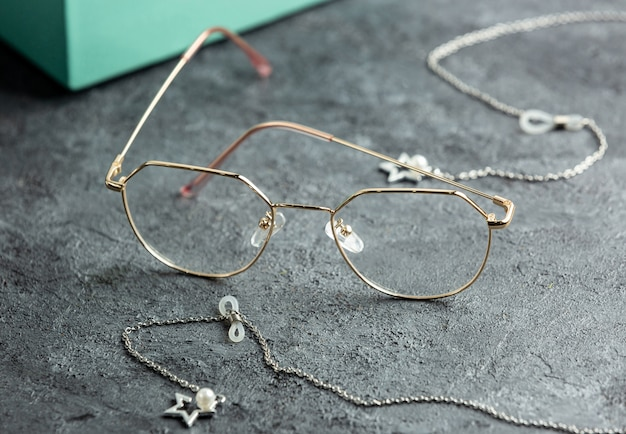 Une vue de face des lunettes de soleil optiques près de la boîte de lunettes de soleil turquoise et un bureau gris avec des bracelets en argent isolé des yeux de vision