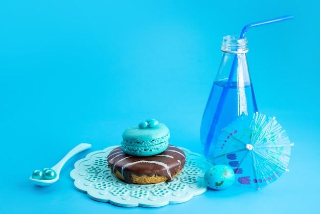 Une vue de face macaron français bleu, coloré avec beignet au chocolat et bleu, boire sur bleu, gâteau biscuit sucre sucré