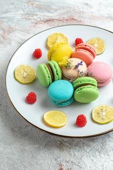 Vue de face macarons français délicieux petits gâteaux avec des tranches de citron sur l'espace blanc