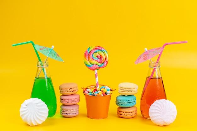 Une vue de face macarons français avec meringues et cocktails sur jaune, couleur biscuit gâteau