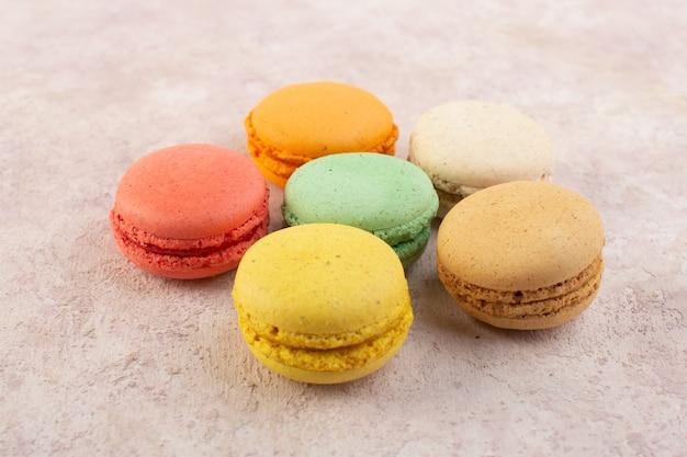 Une vue de face macarons français rond et délicieux sur le gâteau de bureau rose couleur sucre biscuit sweet