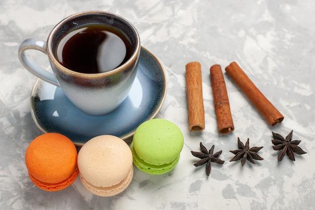 Vue de face macarons français avec tasse de thé sur surface blanche gâteau biscuit tarte au sucre biscuit sucré