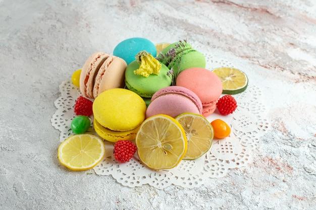 Vue de face macarons français avec des tranches de citron sur un espace blanc clair
