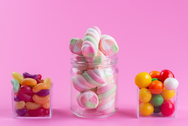 Une vue de face à mâcher des guimauves avec des marmelades colorées et des bonbons sur rose, couleur bonbon sucré