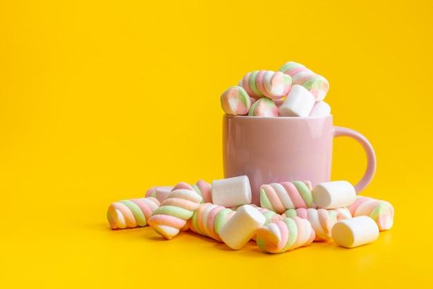 Une vue de face à mâcher des marmelades à l'intérieur et à l'extérieur rose, tasse sur confiture de couleur sucre jaune, sucré