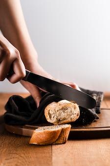 Vue de face d'une main coupant une baguette sur un hachoir