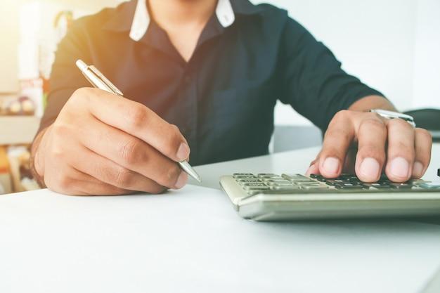Vue de face main homme écrit avec un stylo sur papier et calculatrice tactile. concept de bureau de travail. concept de travail. concept de paiement. compte ou financier. achat ou concept d'acheteur.