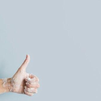 Vue de face de la main savonneuse donnant les pouces vers le haut