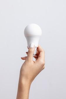 Vue de face de la main tenant l'ampoule avec copie espace
