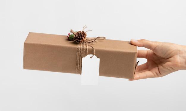 Vue de face de la main tenant le cadeau de noël enveloppé