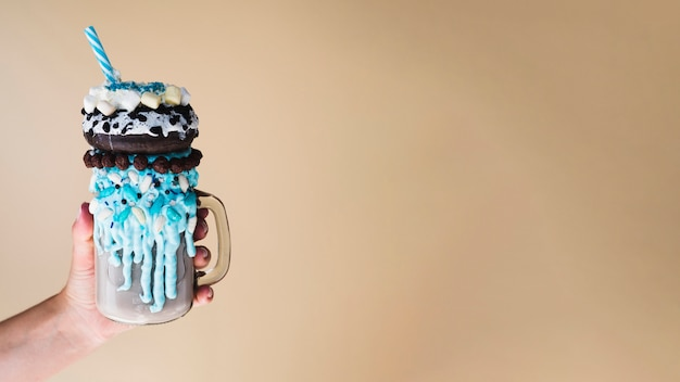 Vue de face d'une main tenant un milkshake avec un fond uni